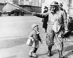 Child and warden wearing gas masks, London, 1941.