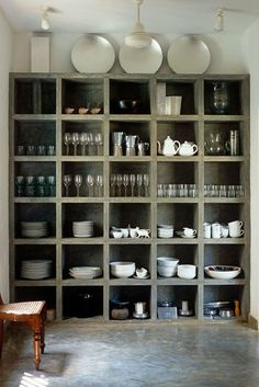 "4. Hiding Dishware. Bowls, cups and plates in the same color family look great showcased in open shelving. Or, as Kutner suggests, you can stack them in serving trays to create a ""sculptural moment"" on the counter"