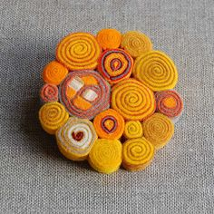 This is a felt brooch... but you could coil strips cut from felted jumpers to make coasters or trivets...