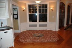 Our customers used our Wright's Ferry brick tiles to frame a mosaic from Moravian Tileworks. The entire design is set into a wood floor in the kitchen. Via Inglenook Tile Design
