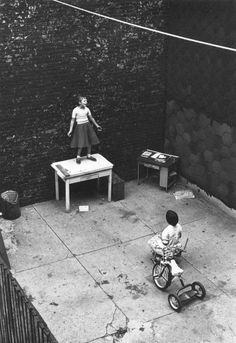 A girl standing on desk in courtyard performing for a seated girl, 1955.  Photo: Wiliam Gedney