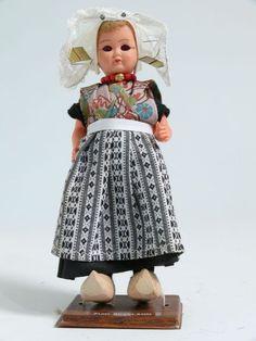 Eine blonde Frau in Tracht von Zuid - Beveland, Niederlande. Schwarzes Kleid mit Schürze, unten schwarz-weiß-gemustert, oben in den Farben Braun, Blau, Grün. Weiße Spitzenhaube und rote Perlenkette. Holzschuhe. #Zeeland #ZuidBeveland