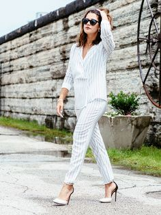 A pinstripe pant suit is paired with high heels and black shades.