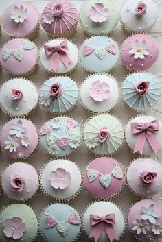 Set of pale green, blue, and pink cupcakes topped with flowers, bows, and mini garlands of hearts spelling out words. Vintage look. Originally done by Cotton & Crumbs Bakery for a christening but could work in almost any setting.