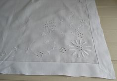 A really gorgeous fine Irish Linen tablecloth with whitework decoration, finished with a deep hemstitched border. Two opposite corners of this lovely cloth are embroidered with a huge single daisy head, lots of eyelets and some finely stitched flower stems.The embroidery is really plump and precise. A 2.25 inch deep border finished with a single row of hemstitch completes this charming piece.  The condition is excellent for a cloth of this age, the linen is very fine, smooth and crisp…