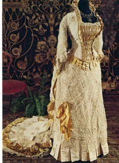 Evening dress, British, ca. 1878-80. This formal evening dress made of white brocade taffeta and gold satin is lavishly trimmed with bobbin lace, ribbon and pleated ruffles. The cuirass bodice is worn over a tie-back skirt which features a low bustle and semi-circular train. Photo by Henry Tabbers. Museum of Vancouver