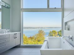Floor to ceiling windows, large floor tiles, a freestanding tub, stainless fixtures and finishes, and a beautiful view