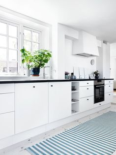 Nordic inspired plain white kitchen with black details, calm colours and clean lines.