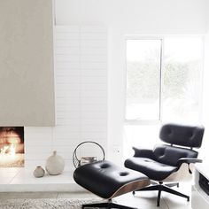 White fireplace and Eames lounge chair. Via Via wit & delight