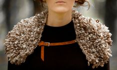 A hand-knit collar is a striking accessory.