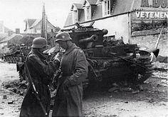 Villers-Bocage. Two germans take a smoke in front och knocked out Cromwell tanks.