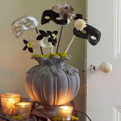 Masked Entrance Display  A stone-look urn resembling a pumpkin makes a lovely anchor for a bouquet of decorative half masks in black, white, and silver. Tuck floral foam into the urn, and press the dowel attached to the mask into the foam. Cover the opening of the urn with green moss. Add votices around the arrangement.
