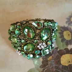 "Beautiful Bling Bracelet The beauty is in the stones used. Different colors of green from citrine colored to clear rinestones.  This bracelet entertains a top of 4 1/2"" wide ? 2 1/2"" covered in color. Back of bracelet is 4"" wide good for up to 8"" wrist.  Hinged. Jewelry Bracelets"