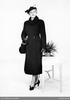 Modell i kappa med krage i persianpäls, hatt med fjäderpenna och flor, handväska, handskar och pumps, står framför ett blombord. Fotograf: Sten Didrik Bellander, ca 1953-1957