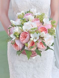 Bridal bouquet with white roses, pink garden roses, and green leaves