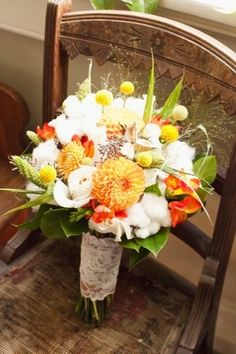 Orange mum.  Yellow billy buttons.  White roses.  Orange alstromeria.  Cotton.