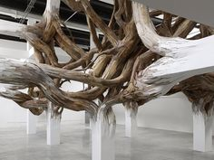 A twisted entanglement of tree branches appears to grow organically from the beams of Paris' Palais de Tokyo museum in this installation by Brazilian artist Henrique Oliveira  #Art #Nature #Organic #Inspiration #Wood #Concrete #ModernLife #OldRoots
