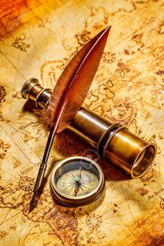Vintage compass, goose quill pen, and spyglass lying on an old..