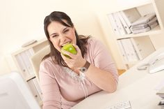 Woman eating apple in office