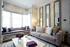 outside mount taupe roman shades | three long wall mirrors with wood trim | window seating area | purple and ivory | home staging ideas