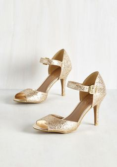Waltzing through a Manhattan mansion, your metallic pumps glisten in the lamplight, earning you a wave of compliments! Elegant ankle straps, peep toes, and a faux-snakeskin finish make these golden heels the perfect portrayal of an exquisite evening!