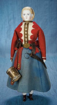 "16"" (41 cm.) Bisque shoulder head with blonde sculpted hair held by a black painted hair band,painted facial features,muslin body,bisque lower limbs,painted brown ankle boots and blue ribbons. The doll is wearing the uniform of the Vivandiere,comprising wool jacket,blue skirt with epaulets,US brass belt buckle,leather purse,drum (originally a candy container) and silver scissors in leather case. The Vivandieres originated in Revolutionary era France,serving the function of tending wounded…"