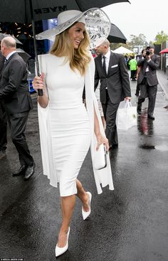 Jennifer Hawkins is still in high spirits as she heads towards the Myer Marquee wearing a wide brimmed hat and long sleeved dress slit on the arm to the elbow