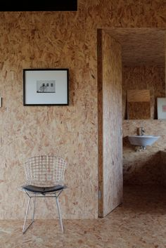 A Pair of English Barns Hide Unabashedly Bold and Budget-Friendly Minimalist Interiors - Photo 6 of 14 - A wire side chair by Harry Bertoia for Knoll sits outside the bathroom in the Stealth Barn. Decor, House Interior, Osb Board, Minimalist Home Decor, Chipboard Interior, Interior, Interior Walls, Osb Furniture, Minimalist Decor