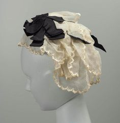 mid-19th century white cap with black bow; wire structure covered with stiff white tape and mesh, black ribbon sewn across top of wire, raw edges of light-weight white silk flounces gathered and sewn to mesh foundation, scalloped and embroidered finished edges of white silk flounces, black ribbon bows at sides (ribbon, warp-faced plain weave silk). Via MFA.