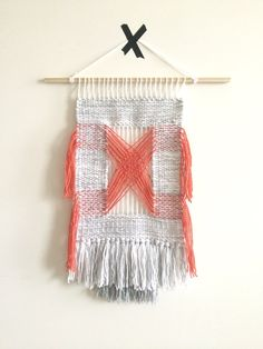 """Criss-Cross  $180.00  Handmade woven wall art with an open center. The open center brings attention to the criss cross the coral yarn makes from traveling from one corner of the weave to the other. This cheerful neutral piece with the pop of coral is sure to bring smiles and positive attitudes from all visitors in your home. Handmade with love.    READY TO SHIP    Acrylic Yarn    Weaving from top of dowel to bottom of fringe: 12""""W x 23""""H  Wooden Dowel: 18""""L"""