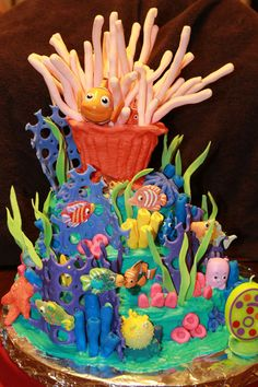 "Finding Nemo cake I made for my son's 6th birthday. Cake is buttercream. The ""reef"" & sea anemone (formed over an empty cream cheese container) are fondant with gum tex mixed in to harden. Other fish are from Disney or gummy candy."