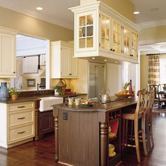 Antique-White #Kitchen | Creamy antique white on the cabinets pairs with a coffee-bean color on the island in this warm kitchen.