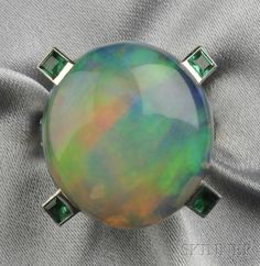 Opal and Emerald Ring, Mounted by Cartier, set with a cabochon opal measuring approx. 22.00 x 20.00 x 9.50 mm, square-cut emerald accents, within a platinum and 14kt white gold mount, signed and numbered.
