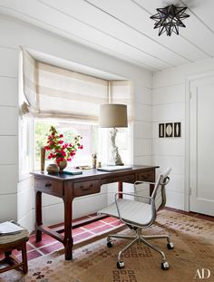 The office features a 1940s plaster table lamp, a 19th-century leather-top desk, an Eames chair from Design Within Reach, and an Afghan flat-weave rug from Woven Accents.