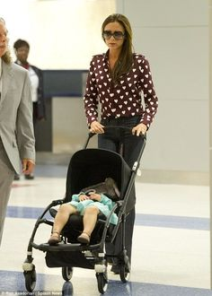 Victoria Beckham wears her heart on her sleeve in patterned dress shirt while carrying Harper through JFK | Mail Online