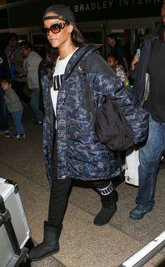 Rihanna wears a Puma t-shirt, sweatpants, camouflage parka jacket, black Ugg boots, Prada sunglasses, and a baseball cap