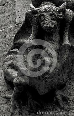 Shot in black and white, detail on a capital with an sculpture  representing a strange creature placed on the facade of this historic building, set in Valencia, España, Spain, Europa, Europe