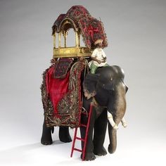 A ceramic model of an elephant, with an embroidered velvet cloth and a metal howdah on its back. The mahout (driver) is shown dressed in a muslin robe and turban, seated on the elephant's neck. | V&A Search the Collections