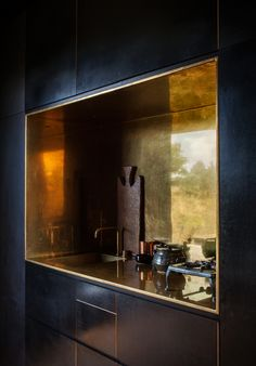 Two Tiny Cabins Chose Simplicity Over Size, The kitchen's brass-lined niche, with a matching tap by Arne Jacobsen for Vola, contrasts the otherwise spare, black formply interior of one of the ca.