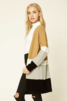 A knit cardigan featuring a color block design, long dropped sleeves, open front, two front pockets, and a longline silhouette.
