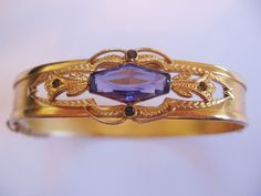 For your consideration a really pretty Victorian Revival goldtone bangle with purple faceted center stone and 4 small round stones. This piece is