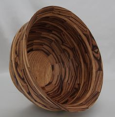 "Segmented Black Limba & Zebrawood Bowl. It contains 109 pieces of wood cut & sanded on the particular angle to make the circle needed for this bowl. It has a durable food safe finish. It is a beautiful piece of art & can be used as functional art by putting fruit etc it it. It would enhance a table or mantel. It is 11.75"" dia x 7.5""H"
