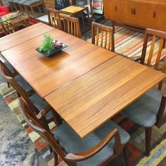 Beautiful vintage MCM teak dining table with leaves that store on each end.  Refinished.