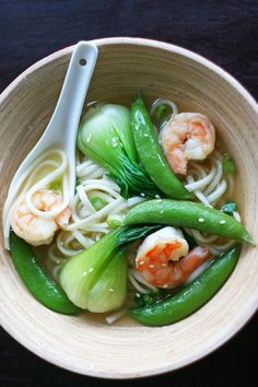 shrimp noodle soup  4 baby bok choy  12 sugar snap peas  12 shrimp, peeled  1/2 teaspoon of grated ginger  1 tbl of peanut (or canola) oil  A pinch of dried chillies  2 cloves of garlic, finely chopped  1 tsp of sesame oil  2 tsp of light soy sauce  2 spring onions, sliced  4 cups of low-sodium chicken stock  Toasted sesame seeds  300 grams of dried udon noodles