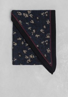 This jacquard knitted triangle scarf in midnight blue features a black and gold leopard pattern and contrasting trims. Made from a warming wool blend.