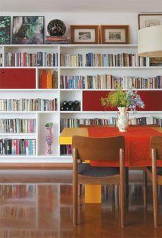 """Bagunça longe dos olhos: Quando o casal precisou transformar o escritório em quarto para Dora, a sala de jantar virou espaço de trabalho. """"Escondemos a bagunça de cada um em dois nichos compridos da estante, fechados com as portas vermelhas"""", diz Joana. Cadeiras do designer Fernando Jaeger."""