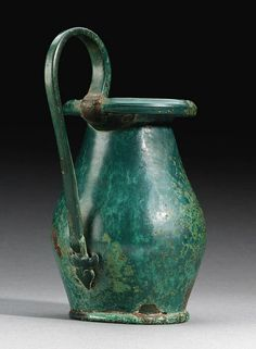 AN ETRUSCAN BRONZE OLPE   circa 5th century b.c.   The piriform body on an flat base with a rounded edge, the wide mouth with a thick rounded rim, the high vertical cast handle riveted in place below the rim, the terminal in the form of a winged siren, the details worn  6.7/8 in. (17 cm.) high