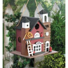 The birds will love making a nest in this charming two-story fire station bird house! The outside is decorated with a hose, ladder, and a hydrant right outside. Painted wood, plastic, and jute hanger