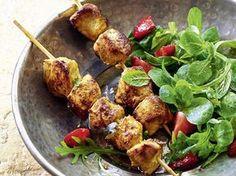 Indische Hühnerspieße auf Blattsalat mit Erdbeeren