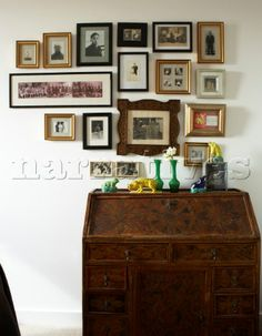 Antique bureau with collection of framed family photos and memorabilia